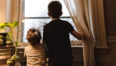 A brother and sister through single parent adoption look out the window.