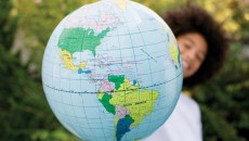A child with a globe, representing a homeland trip