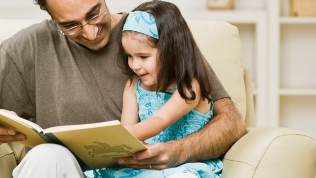 Father reading with his daughter to ward off language impairment