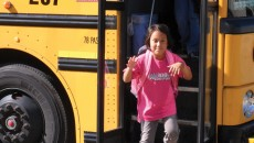 A child getting off a school bus, prepared to discuss race in the classroom