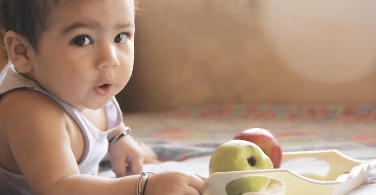 Baby with apples, symbolizing adoptive nutrition