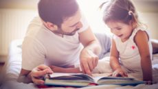 A dad works on building reading skills with his daughter by reading a book together.