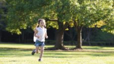 A resilient girl runs outside in a park.