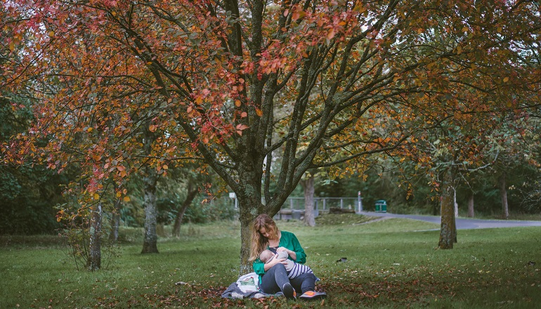 A woman sits in a park, breastfeeding an adopted baby