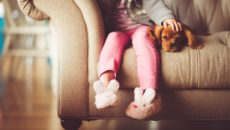 A child sits on the couch and wants privacy, a natural phase of the stages of childhood