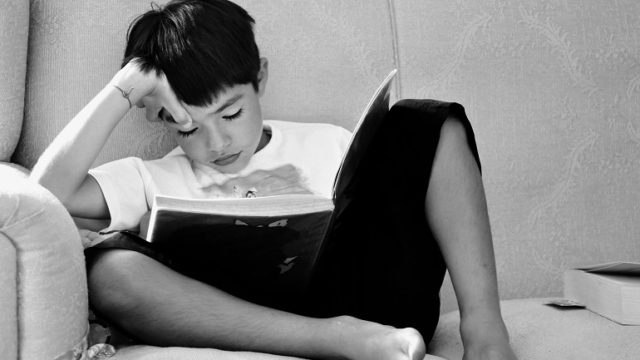 A grade school age boy reading books on adoption