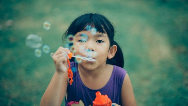 A girl blows bubbles and thinks about transracial families.