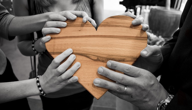 A group of people stand together, holding a wooden heart after adoption reunions