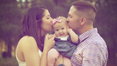 Two parents kiss their infant on the cheeks after preparing for a baby to adopt for so long.