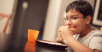 A child eating and overcoming food insecurity