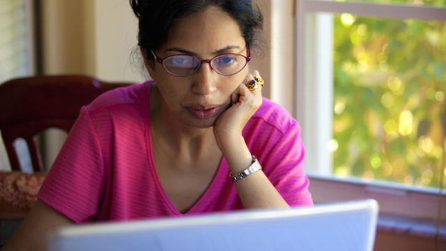 A prospective adoptive mom reading adoption websites on her laptop computer