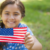 a girl who was adopted internationally but is now a U.S. citizen holds an American flag