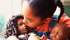 An African-American girls plays with two dolls that reflect her race